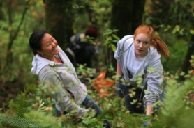 by: DENISE FARWELL, Sunset High School students Hyo-Jung Na (left) and Katie Litvin, both 17, watch on a Saturday earlier this month as one of their schoolmates crosses an ivy-covered slope in Forest Park. When they were done volunteering to remove the invasive plant, there was less to navigate, and more chance for trees to survive.