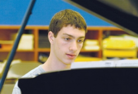 by: Carole Archer, Daniel Koch relaxes when he sits in front of a piano. The Barlow senior, who teaches piano lessons, is up for a National Merit Scholarship.