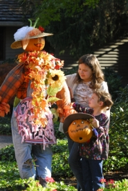 by: Vern Uyetake, Audrey and Miranda Jones put finishing touches on their scarecrow, complete with a scarf made from maple leaves.