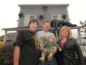by: Vern Uyetake, Brittnay Macom and her husband Thurston Macom — holding their son Holden — stand with Thurston's mom Molly Macom outside Westlake Properties in West Linn. For years the family has decorated the real estate building for holidays.