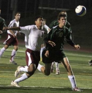 by: JAIME VALDEZ, IN THE AIR — Tualatin senior Omar Cuevas (left) and Tigard senior Roland Mason race for the ball in last week's match. The Timberwolves scored a 3-0 victory.