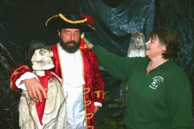 by: Marcus Hathcock, Sandy Mountain Festival Spook Trail organizer Martin Montgomery gives a sneak peek of the pirates section of the trail, as Vicky Mills straightens his parrot.