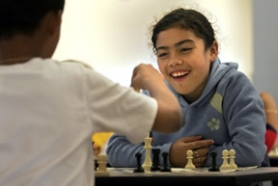 by: Jaime Valdez, Fourth-grader Kathy Madrigal-Villegas challenges Jose Alvarado in chess during the after-school programs.
