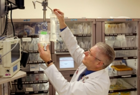 by: L.E. BASKOW, Jerris Hedges, an OHSU emergency room doctor, hangs a bag of normal saline solution next to a new hypertonic test solution (left). The test solution has a greater salt content.