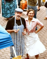 by: David F. Ashton, Celtic Sheppard Creamery's Brendan Enright (in the striped apron) visits with People's Co-op farmer's market coordinator Ariana Jacob (wearing the hoop skirt) amid the bustle of market's Harvest Festival.