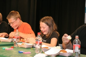 by: Steven Kenner, Contestants in the onion eating contest.