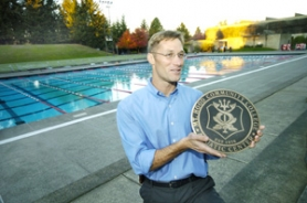 by: Carole Archer, Mt. Hood Community College Aquatics' Director Brandon Drawz displays a bronze marker that people can purchase for $5,000 to help fund improvements to the swimming complex.
