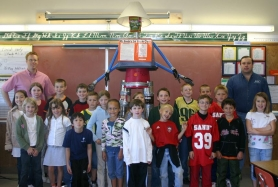 by: Garth Guibord, Richard Phillips, far right, won the silent auction for the recycling-themed scarecrow and then gave it back to the third grade class who made it. Teacher Chris Goede stands at far left.