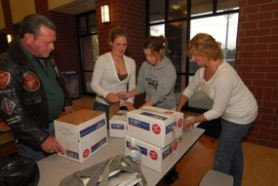 by: Vern Uyetake, Assistant coach Rick Groulx, far left, and team mom Judi Colson, far right, were on hand recently to help the Lake Oswego girls soccer team pack care packages for some of our troops stationed in Iraq. Colson's son Devon is there working as a jet mechanic for the Marines.
