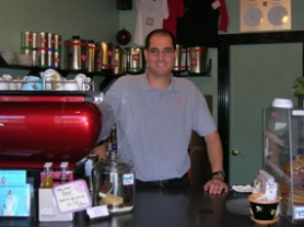 by: Lee van der Voo, Nathan Spaccarelli, owner of Café Marzocca, is also the exclusive distributor of illy coffee in the Northwest. His repeated struggles with city code make him leery of the Lake Grove Village Center Plan and other city-sponsored plans.