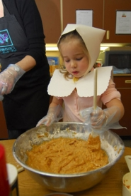 by: Vern Uyetake, Dressed in handmade pilgrim garb, Savannah Bailey stirs a mixture that will become pumpkin muffins for her class to enjoy at their Thanksgiving feast.