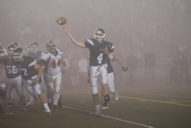 by: Vern Uyetake, Lake Oswego quarterback Duncan White, far right, delivers a touchdown pass to Franklin Forward early in last Friday's playoff game against Westview. A thick layer of fog, which can be seen in the background, hindered Lake Oswego's ability to pass later in the game. It hardly mattered, though, as Lake Oswego chalked up a convincing 17-3 victory over the Wildcats. Next up will be a quarterfinal matchup against Grant. The game will be played Friday at 7 p.m. at Lake Oswego District Stadium.