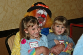 by: John Saxman, A member of the Rose City Clowns enjoys a special moment with two young ladies at the party.