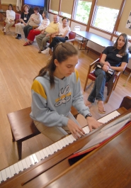 by: Vern Uyetake, Alexis Burris plays while her sister Lydia listens at a recent session of the ACC Respite Program. Talented volunteer entertaineers like the Burris sisters have helped make the program a success.