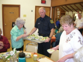 by: Cliff Newell, Lt. Paul Lorenzen of the Lake Oswego Fire Department helps serve at the ACC Thanksgiving Lunch. The annual event drew a capacity crowd of senior citizens, families and friends.