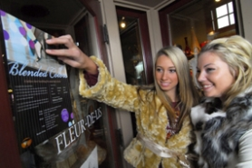 by: Vern Uyetake, Danielle Meyer, left, and Ali Super hang up a poster for their upcoming fashion show titled Blended Colors, which benefits a Rwandan high school. Meyer wears a gold Mac and Jac fur coat and vintage long-sleeved top from Fleur De Lis, a West Linn boutique participating in the event. Super's fur vest is from the brand By Deep.