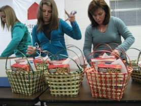 by: Submitted photo, National Charity League of Lake Oswego members, from left, Maddie Ingram, Colleen Hefferman and Tricia Hefferman assembled Thanksgiving baskets for Metropolitan Family Services to distribute to low-income families.