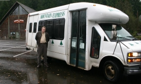 by: Garth Guibord, Villages board member Bob Reeves admires two of the villages' supported activites: the Mountain Express bus and the Dorman Community Center.