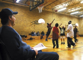 by: JIM CLARK, Sports coordinator Dave Higgs watches as students shoot hoops at the NAYA gym. The facilities at the former Whitaker-Lakeside Middle School allow for many more activities than NAYA's North Mississippi Avenue offices did.