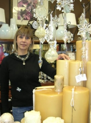 by: Lee van der Voo, Tania Thompson, owner of the new Lake Grove shop Style Obsession, shown with oversized house candles. The boutique offers urban yet worldly fashions in clothing and home accessories.