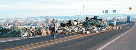by: Submitted Photo, Oregon State Trooper John Russo surveyed the damage Sunday afternoon as bee hives littered Highway 97 in Central Oregon after a flat-bed truck driven by an Aloha man overturned.