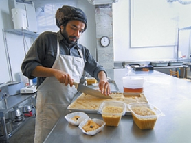 by: VERN UYETAKE, Yashar Mosanen, of Caspian Blossom, cuts up halvah, a traditional Middle Eastern sweet confection, for sale. In the foreground are containers of brown rice pudding, made from his Iranian mother's recipe, and his chocolate organic baklava.