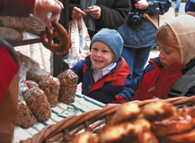 by: JAIME VALDEZ, A farmers market isn't a summer-only affair at People's Co-op, where 3-year-old Oscar Goodrich (left) gets ready for a fresh Fressen Bakery pretzel while Lee Kametani sorts through Jerusalem artichokes (below, left). Other fresh goods like Asian greens (below, middle) are available outside, and there's more inside the market.