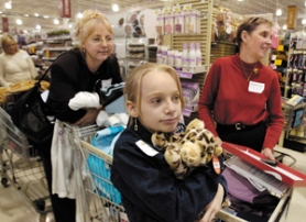 by: Carole Archer, Volunteer shoppers Linda Tomar, left, and Gayle Morris assist Linzey Oulman, a fifth-grader at Butler Creek Elementary School, as she checks out at the Hollywood Fred Meyer this week.