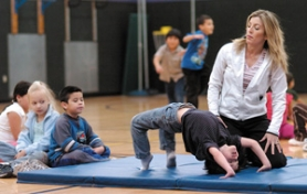 by: Carole Archer, Physical Education Teacher Jennifer Griffin instructs Adrianne Gronnert's first-grade class on how to do back flips. Students from left, Gisel Moron, Ida Fogel, Juan Garcia Flores and Kason Rondot on the mat.
