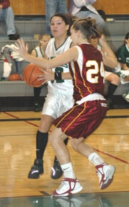 by: Clinton Vining, Senior Kayla Adamson drives against Junction City's Kayla Rauschert.