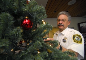 by: VERN UYETAKE, Chuck Chaffin, deputy fire marshal with the Lake Oswego Fire Department in downtown Oswego, examines a strand of holiday lights on a Christmas tree. Lights produce heat — and if your Christmas tree is dry enough — could start a fire.