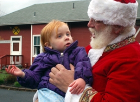 by: Barbara Adams, Peter Tuomala, right, as Santa Claus, holds Mia Richman at the Troutdale Farmers' Market on Saturday, Dec. 9.