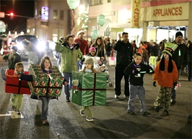 by: Chase Allgood of the NewsTimes, Gift-wrapped students from Dilley Elementary School – and their parents – joined dozens of other entries in last Wednesday's Holiday Light Parade in downtown Forest Grove. Despite near-freezing temperatures, hundreds of spectators lined the streets to take in the action.