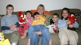 by: Marcus Hathcock, Always active, the family of five adopted children takes a few minutes to get settled on the couch for a photo. From left, David, 9; Janessa, 3; Enrique, 3; Mindy; Jacob, 5 and Jordan, 7.