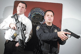 by: Jaime Valdez, Beaverton Police Officers Andrew Halbert and Mike Hanada hold examples of replica firearms police encounter when on some emergency calls. Halbert holds an H&K G36 assault rifle replica while Hanada holds a Berreta 92F that looks real.