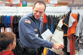 by: Jonathan House, SANTA IN UNIFORM — Lt. Glen Scruggs of the Tigard Police Department helps Joey Shaw of Brookwood Elementary find the right shirt during Fred Meyer's annual Christmas for Kids event in which students got clothes and toys plus items for their siblings.
