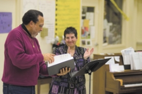 by: Carole Archer, Gresham Community Choir Director Annette Steele applauds tenor Chrisler Hodge's solo during rehearsal Monday, Dec. 11.