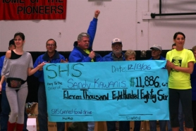 by: shelly anderson, Sandy Kiwanis President DJ Anderson rejoices as Sandy High School presents the organization with a check for $11,886.69, obtained during the canned food drive.