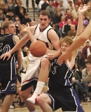by: Vern Uyetake, Lake Oswego's Kevin Love does battle with South Medford's Kyle Singler underneath the basket in Friday's semifinal game at the Les Schwab Invitational. South Medford won 71-63.