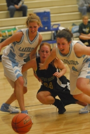 by: Vern Uyetake, Lakeridge's Kirah Aldinger-Gibson, left, and Amanda Huck, right, fend off West Linn's Emily Locke as the three players chase a loose ball during Three Rivers League action Tuesday night. West Linn stalled much of the fourth quarter en route to a 45-41 victory.