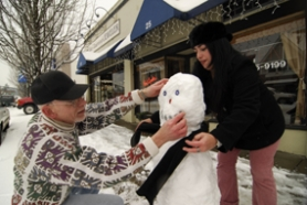 by: Vern Uyetake, Dennis Winslow, owner of Archie's Pub in downtown Lake Oswego, team up on building a snowman with Lila Jane Clary Tuesday afternoon in front of the A Avenue tavern.