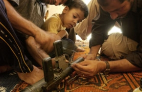 by: Thorne Anderson, A young boy in Sadr City watches his relatives repair a rocket-propelled grenade launcher in the home of a Mahdi Army fighter. Photo by Thorne Anderson; Aug. 7, 2004.