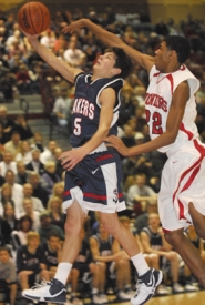 by: Vern Uyetake, Lake Oswego's Landon Ainge, left, keeps the ball just out of reach of a Oregon City defender during last Friday's key TRL game. The Lakers won the game 72-50 to take sole possession of first place. Center Kevin Love led the way with 39 points, including 21 in the fourth quarter.