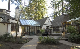 by: Vern Uyetake, Ellyn Bye's 1929 house in Lake Oswego twists and turns to surround beautiful gardens and a large patio. A glass transition room connects the original home — on the right — with the new master suite on the left.