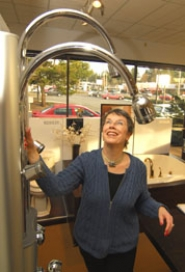 by: Vern Uyetake, Sue Blatner, showroom manager at Ferguson SuperBath in Beaverton, demonstrates the Water Haven, an easy-to- install unit with faucets that can raise or lower. Temperature and volume controls can be adjusted for each person.