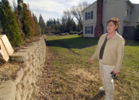 by: Vern Uyetake, Katie Bullard says a public pathway through her property is proposed to line this wall, the same place she plans to put a driveway if an application to partition the land into three lots is approved. Bullard is fighting the pathway requirement and getting the attention of neighbors who are concerned about their property rights.