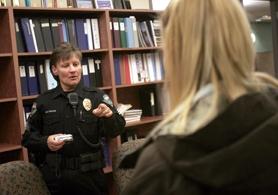 by: Jonathan House, BUSTED — Sgt. Royanne Mathiesen of the Tualatin Police Department instructs an underage decoy on what can be carried in her pockets during a night of alcohol stings.