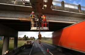 by: L.E. BASKOW, Inches from speeding traffic, ODOT's Dave Henkes and Dave Oliver repair a girder on the Glencoe Road overpass that crosses U.S. Highway 26 after the span was damaged by an oversized vehicle.