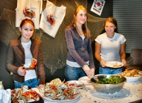 "by: David F. Ashton, Serving up the crabs are students Hannah Giger, Elizabeth Van Brocklin, and Sarah Menashe, at the CHS ""Claws and Dogs"" fest."