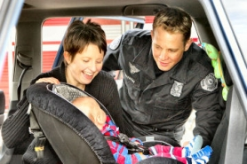 by: David F. Ashton, Sellwood's Heather Hunt learns how to properly use Parker's child safety seat from Portland Police Officer--also a father--Brett Barnum.